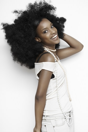 Woman with huge afro in white smiling featured