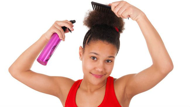 Young black girl spraying water on her afro puff