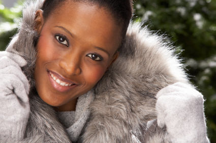 Fashionable Woman Wearing Fur Coat In Studio In Front Of Christmas Tree