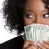 Curly haired woman holding a fan of dollars against her face