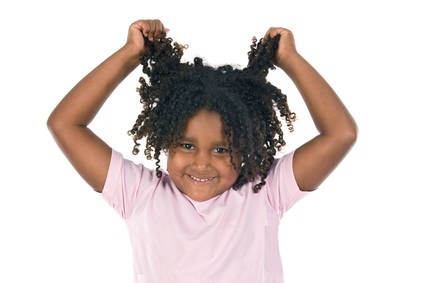 Young black girl pulling on her curly hair