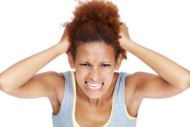 Very frustrated and angry woman pulling her natural hair