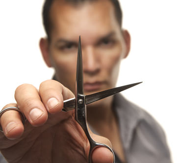 Male hair stylist holding steel cutting scissors