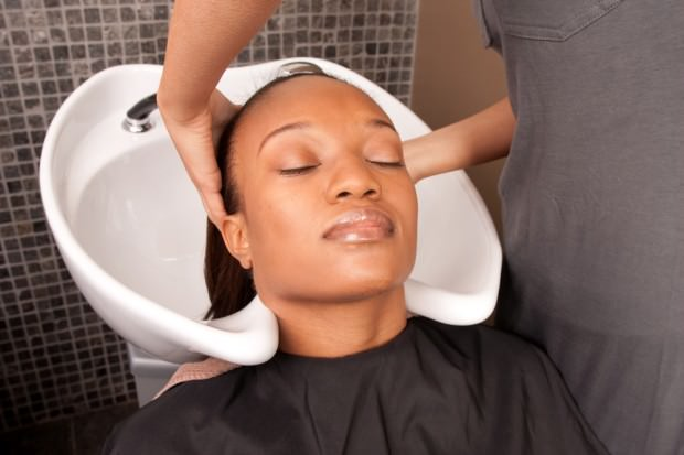 Woman having her relaxed hair washed at the salon