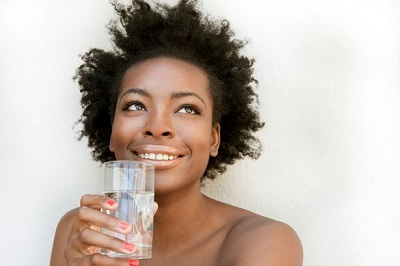 African American woman holding a glass of water