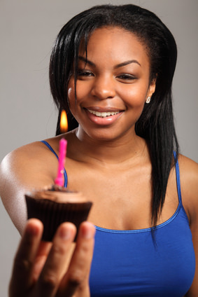 Beautiful young black girl with birthday cake