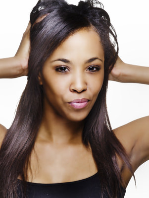 Woman with relaxed hair holding head in hands