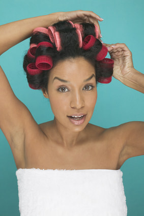 African American woman in towel putting rollers in her natural hair