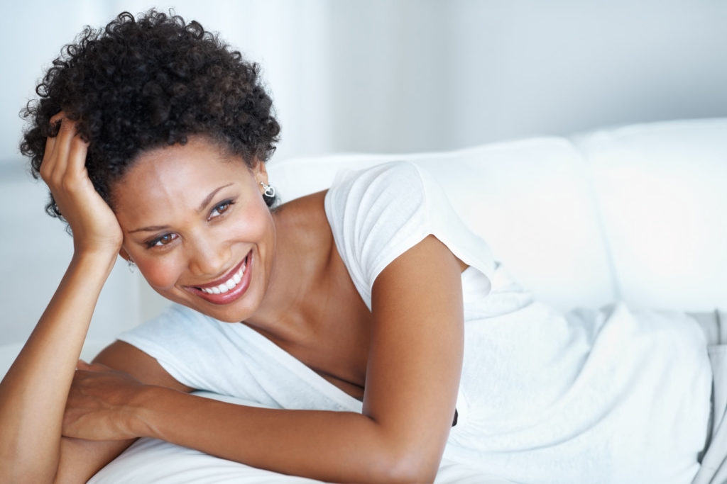 Smiling woman with natural hair relaxing