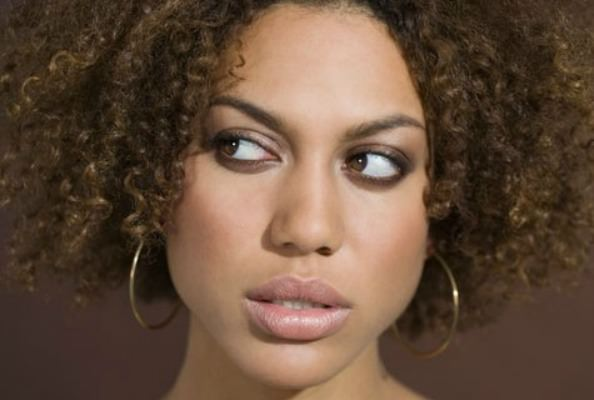 African American woman with curly hair looking confused
