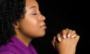 Black woman in  purple top praying