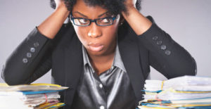 Stressed black woman with a pile of papers on desk