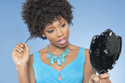 Attractive African American woman looking at herself in mirror pulling her curly hair