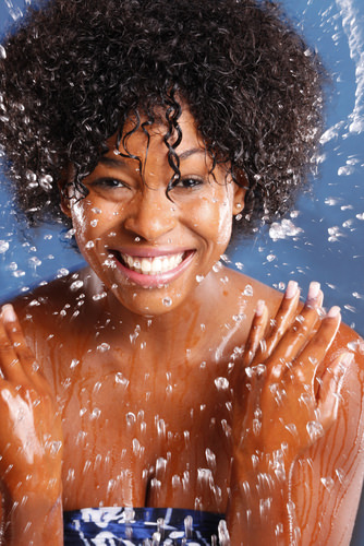 Black woman with wet natural hair splashing water
