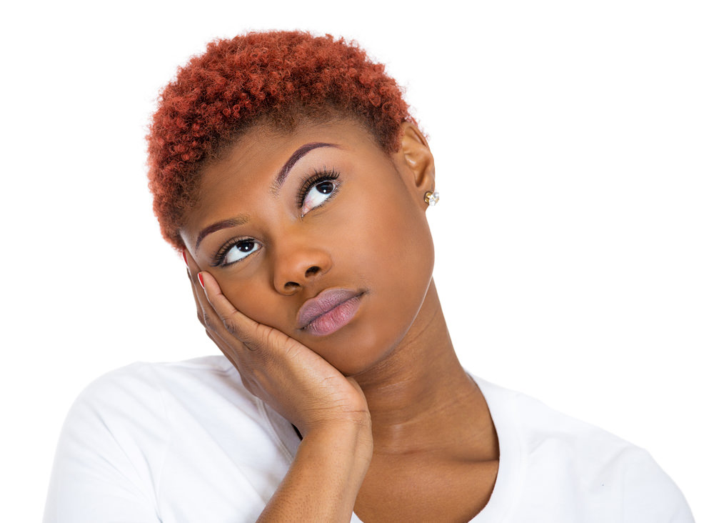Woman with short colored natural hair looking thoughful
