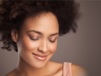 Woman with kinky natural hair eyes closed smiling