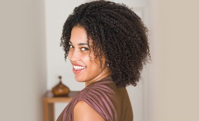 Woman with kinky curly natural hair smiling